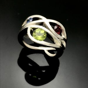 wave ring design with birthstones on black back ground